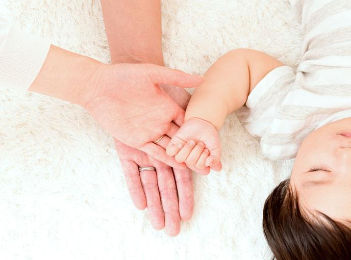 寝ている赤ちゃんとお父さんとお母さんの手