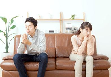 そっぽを向いてソファに座っている男女